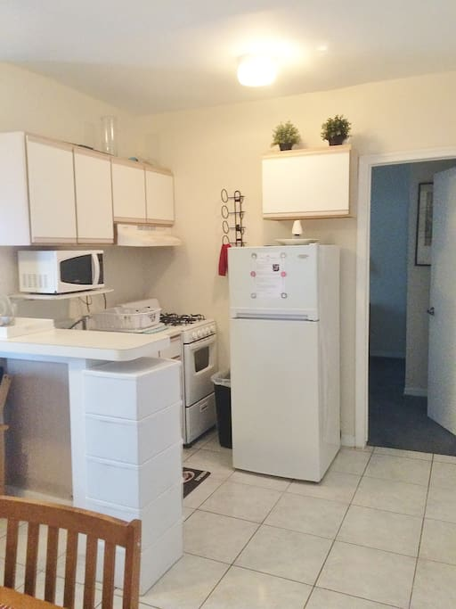 Full kitchen with oven, microwave and fridge.