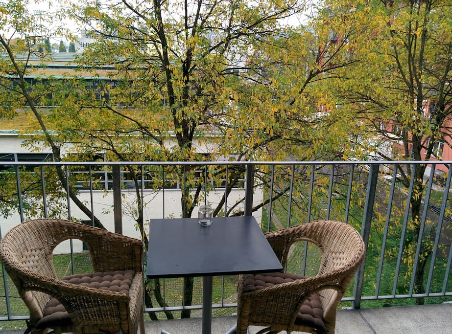 Cozy balcony with a small table and 2 chairs.