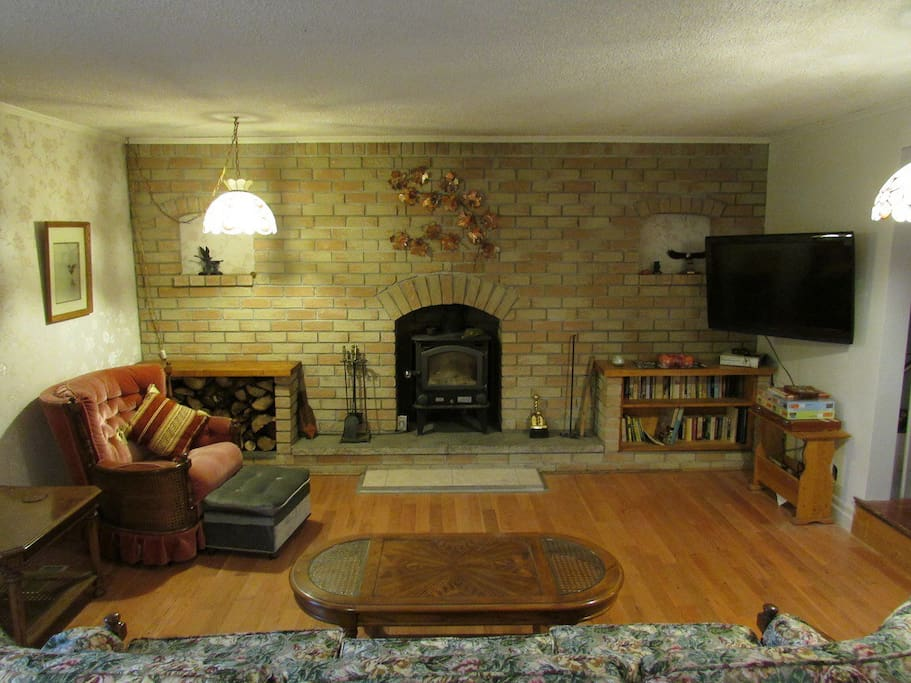 Large living room with pull out couch, flatscreen tv and wood burning fireplace. Also accesses large deck with BBQ.