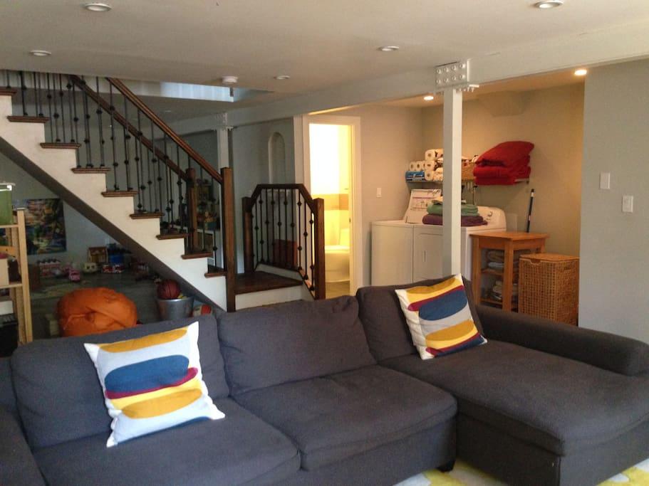 Downstairs living room, washer/dryer, playroom, half bath.