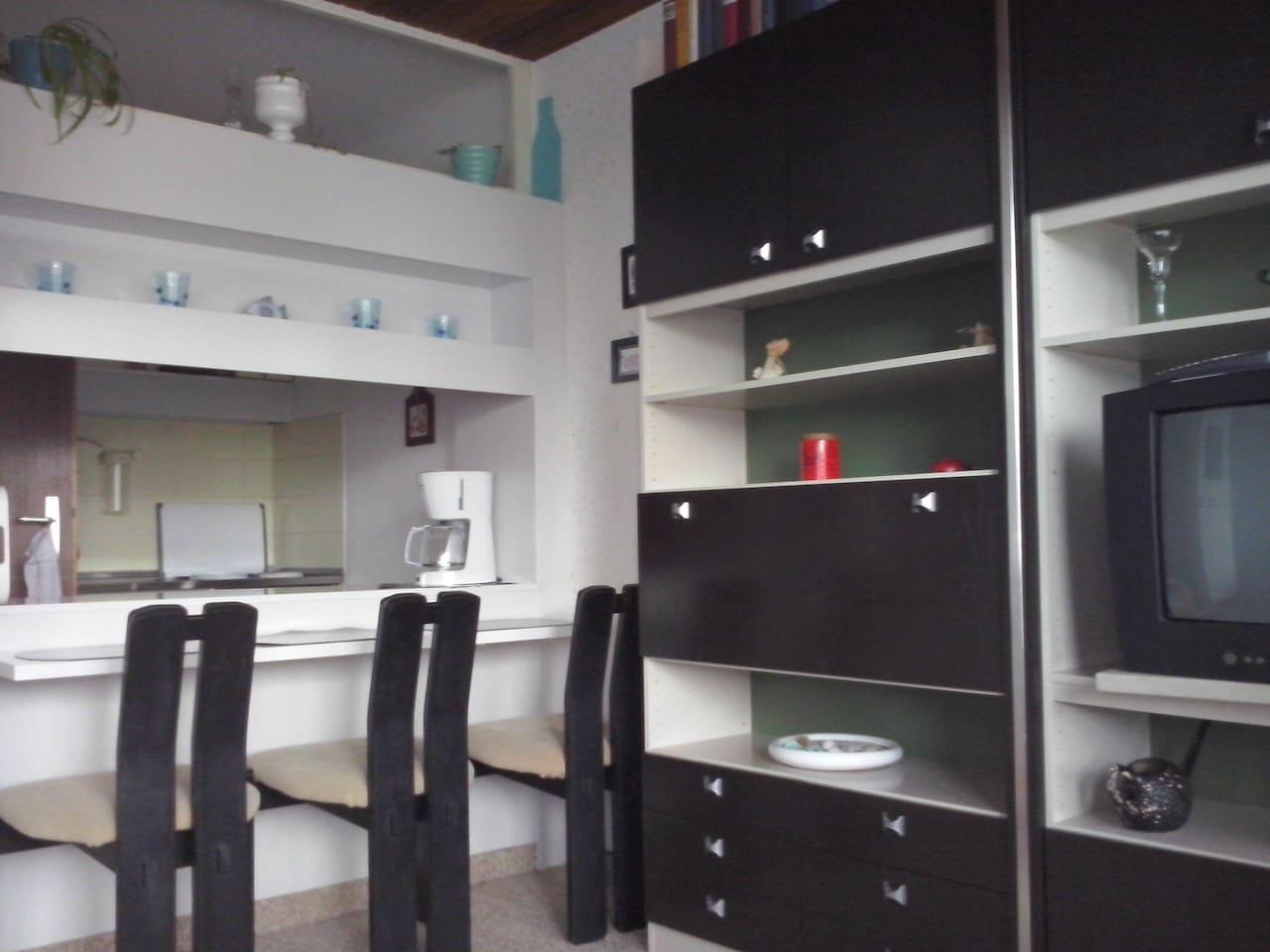 Hinter der Eßtheke sieht man die Küche, welche links eine Tür hat. Rechts eine Schrankwand mit TV