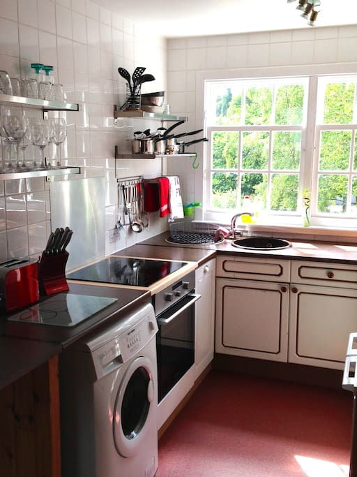 Open plan kitchen with dishwasher, oven, hob, washing machine, microwave, etc.