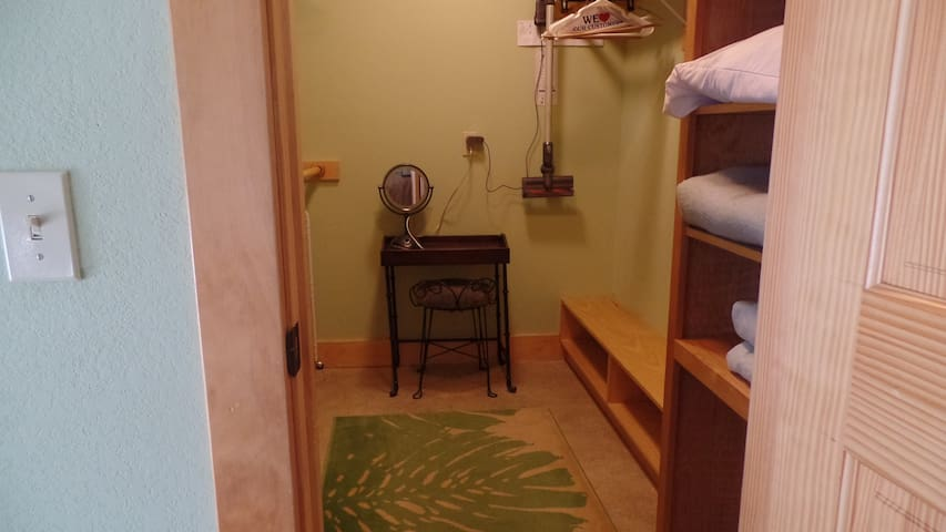 Looking into large walk in closet complete with make up table/grooming area.