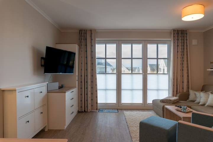 Wohnzimmer mit Blick auf den Balkon. Links steht der großzügige Schuhschrank.