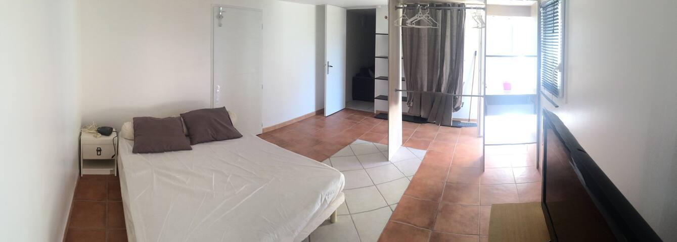 Pièce chambre avec petit dressing, bureau et étagère.
