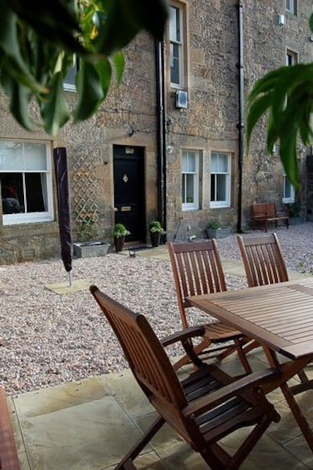 Dining area of courtyard garden with patio furniture and BBQ