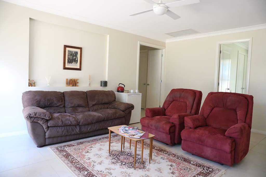 Guests living area containing tea and coffee making facilities, magazines and television with access to the huge deck and overlooking the rear of our 1 acre property.