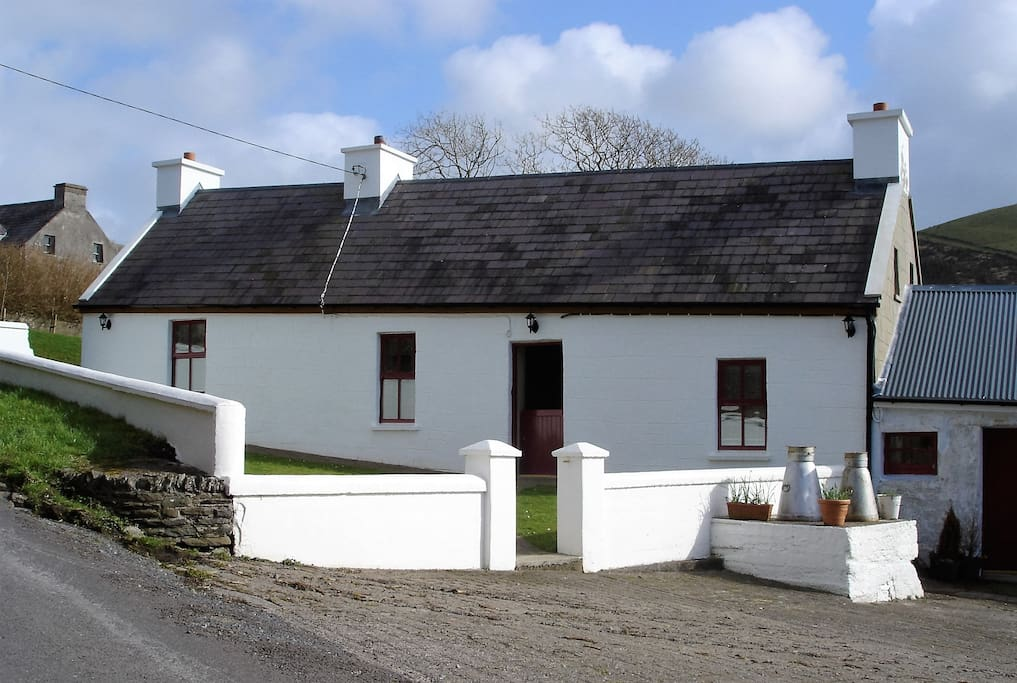 Front side view of cottage. Garden enclosed with a wall.