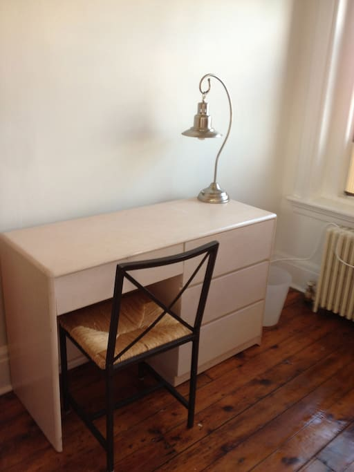 Desk with caned chair for comfort.