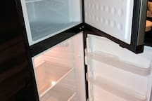roomy refrigerator/freezer in kitchen.  On top of it sits a large toaster oven which also broils and bakes.