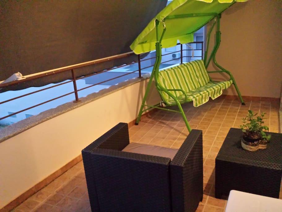 terrazzo con dondolo e attrezzatura per il mare (ombrellone, giochi spiaggia, frigo portatile, sdraio spiaggia)