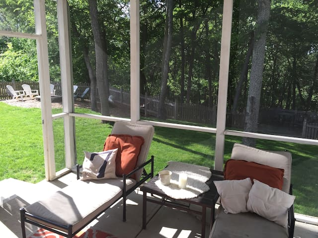 Screened porch overlooking fenced in backyard with deck, firepit and hammock overlooking woods. One of our favorite spaces to hang out!