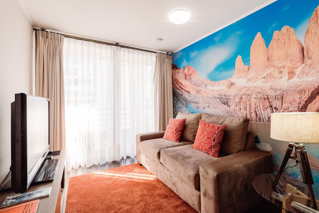 """View of the Living room, wall paper is a view of """"Torres del Paine"""" in the South of the country during the summer season"""
