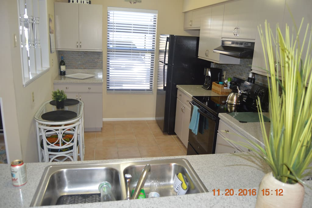 Spacious kitchen with solid surface countertops and new appliances