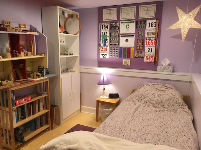 Inner part of bedroom with twin bed (and dollhouse)