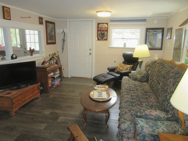 In Summer, the living room has 2 recliners and a comfortable couch to watch Dish TV or play a game from the old time entertainment center! The pass through to the kitchen gives you lots of room for snacks when you are watching something on TV.