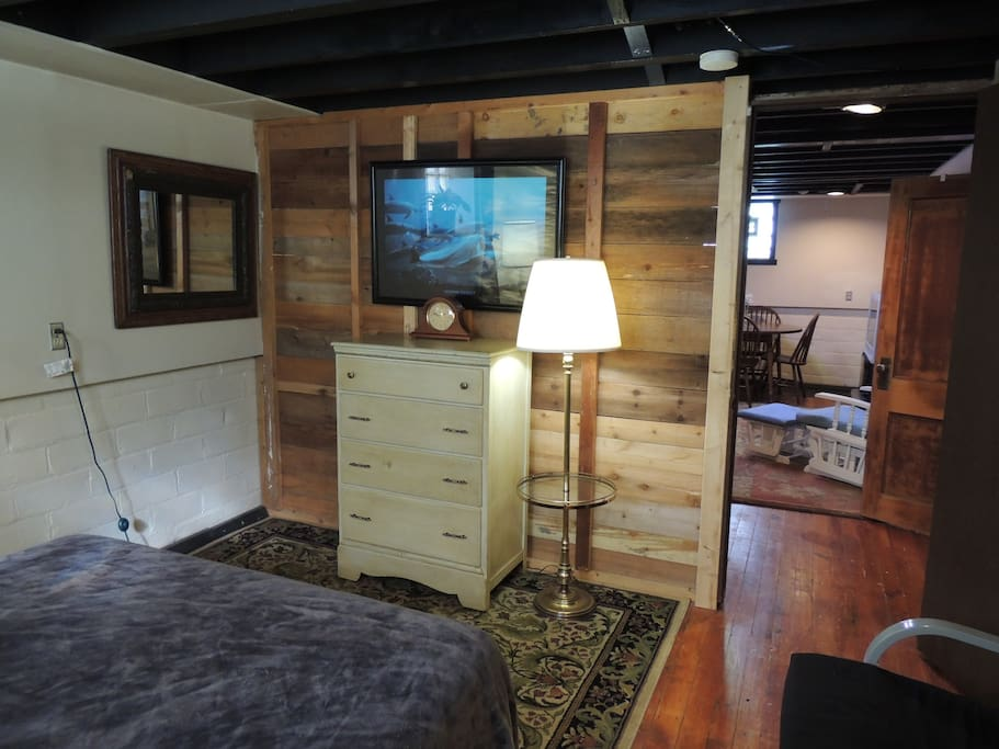 View of the large private bedroom showing the upcycled wall, artwork, mirror, lamp, and dresser