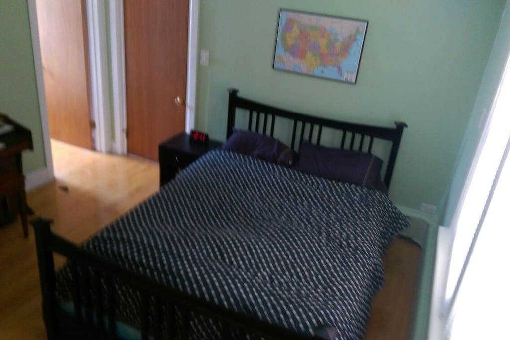 Bed with open closet door.  The closed door leads to the back door, which can be a private entrance, if desired.
