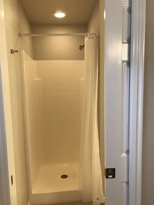 Stall shower with sliding door to bathroom.