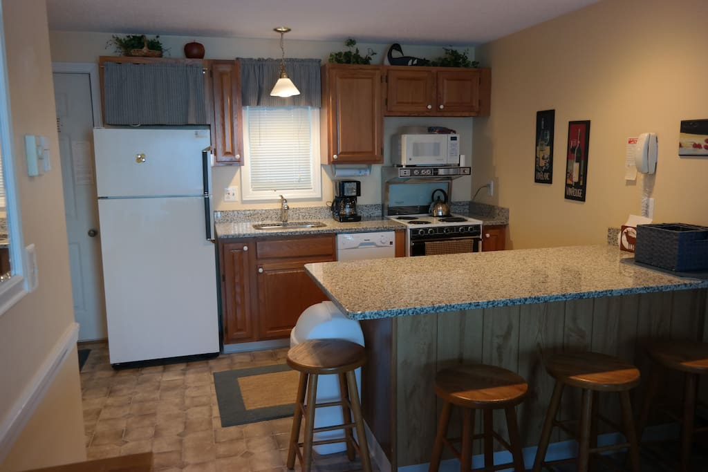 Fully stocked, well-lit kitchen sporting new granite peninsula with 4 bar stools.