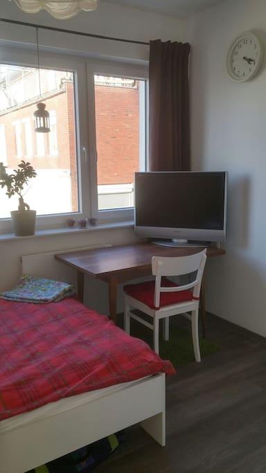 Gästezimmer mit Tisch und Fernseher