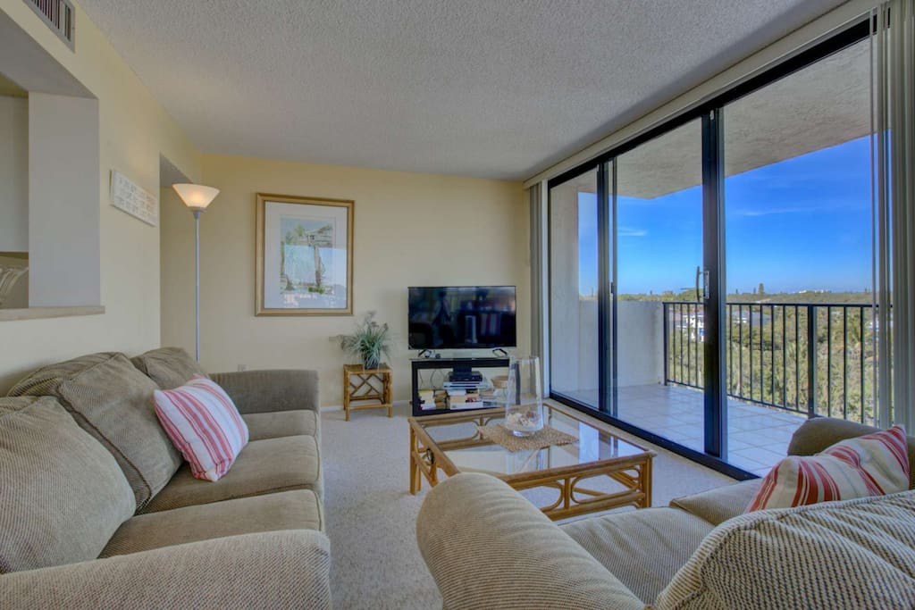Living room with sliding door to wrap around balcony.  Enjoy being entertained by the large flatscreen TV.