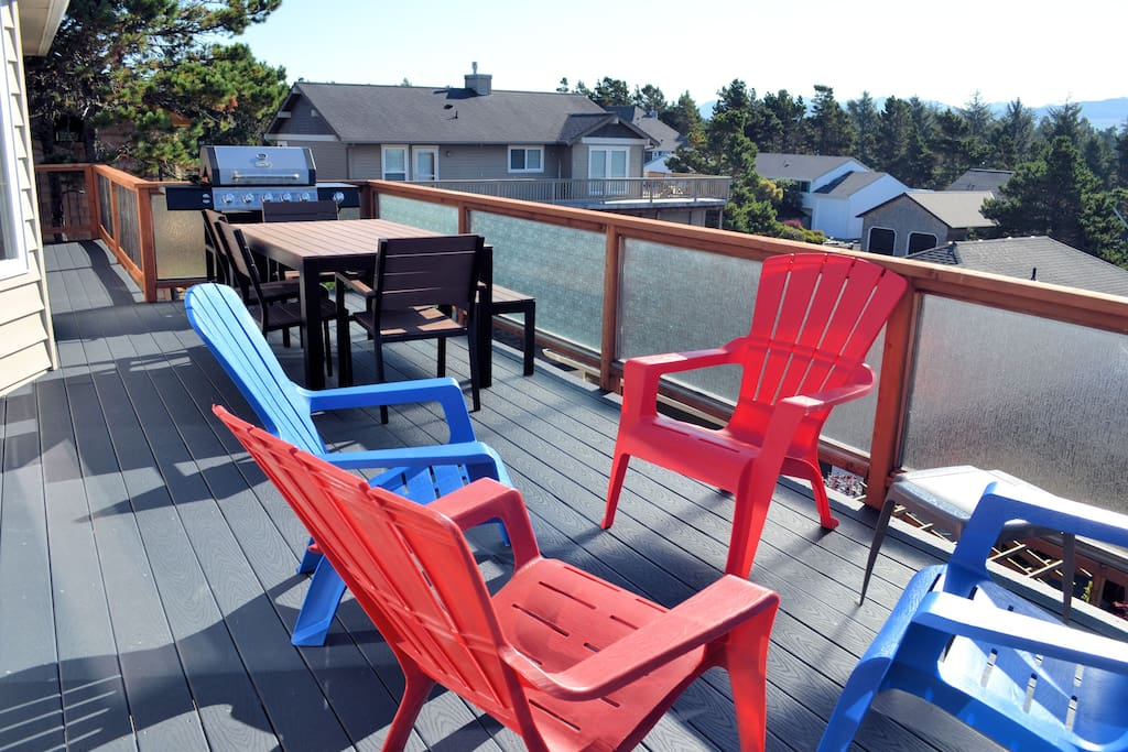 Upper back deck that has seating at a table with 4 chairs and bench seat, 4 plastic patio chairs, and gas BBQ