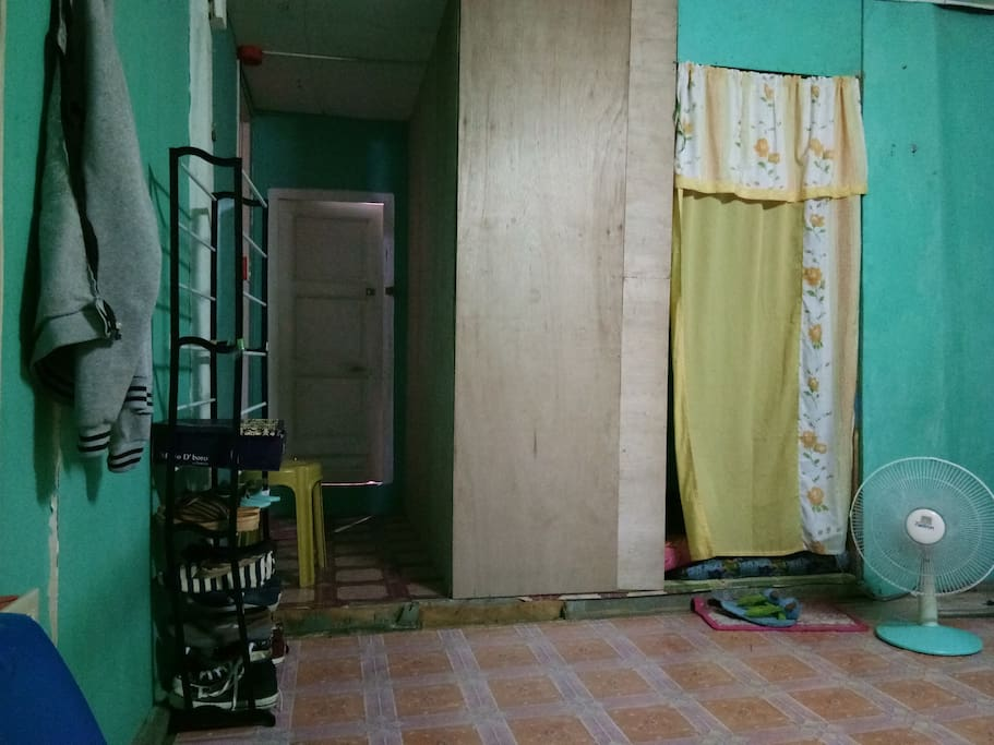 the white bach door is wer the guest can stay..its a room.. beside is the comfort room.. the one with yellow curtain is our room.. she/he can also use shoe racks