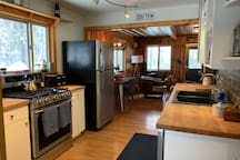 Open kitchen with oven, fridge and dishwasher.