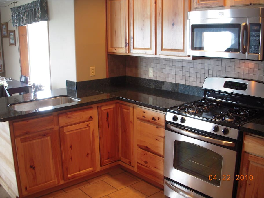 Fully stocked gourmet kitchen with granite counters and stainless appliances.