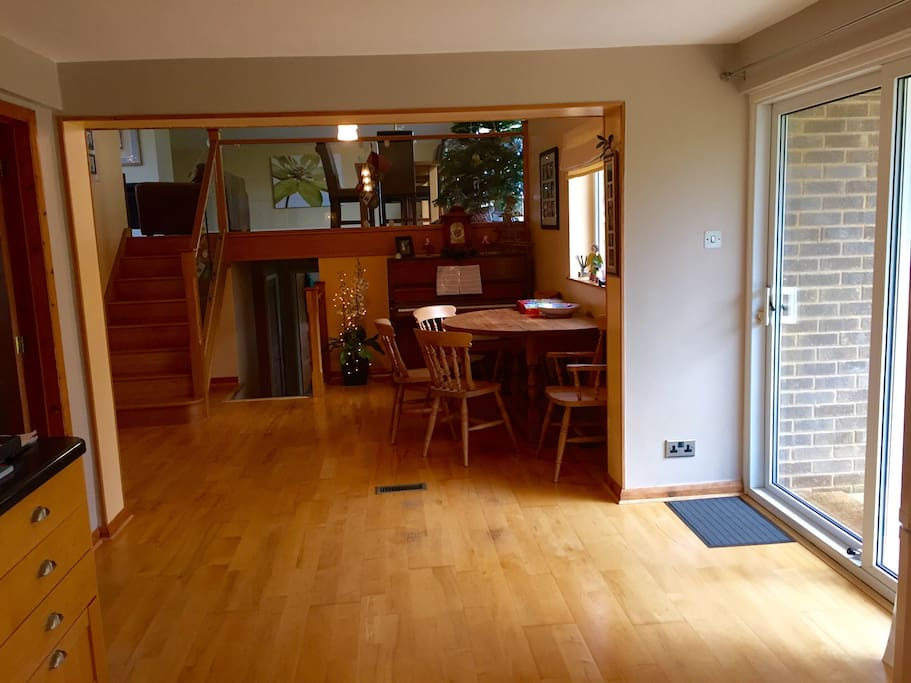 Looking from kitchen to dinning room, with living room up the stairs and bedrooms down stairs. Sliding doors to right leading to decking and garden.