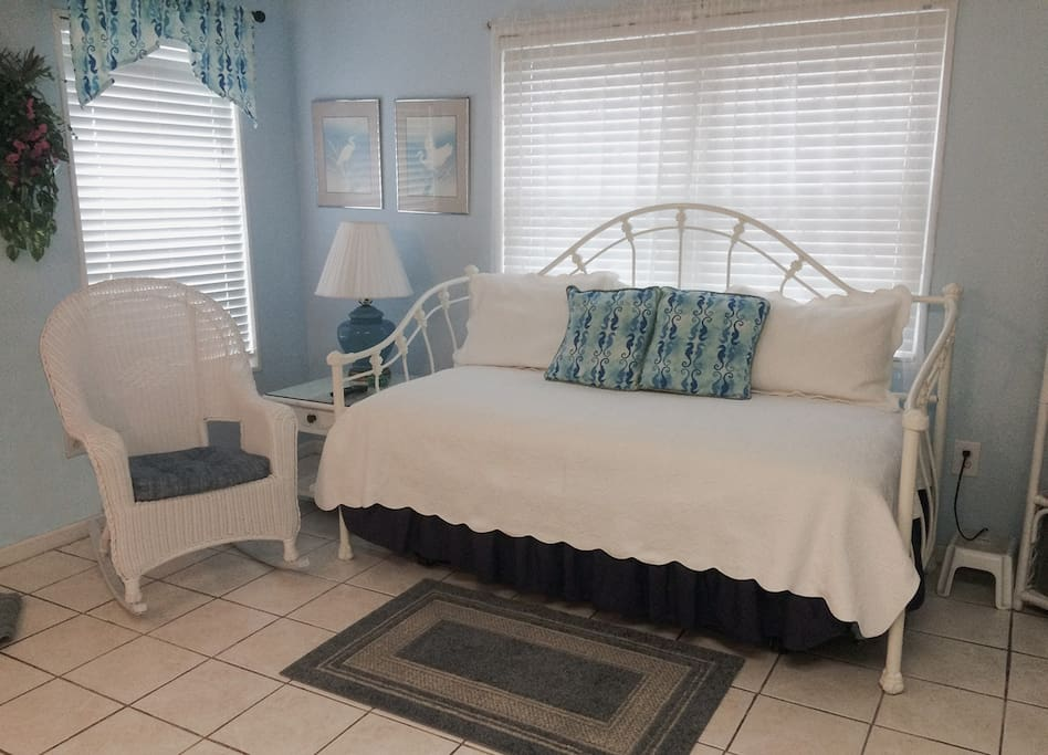 The living room features a wicker rocking chair and comfortable daybed  for relaxing after a day at the beach. There is a trundle to sleep an extra guest.
