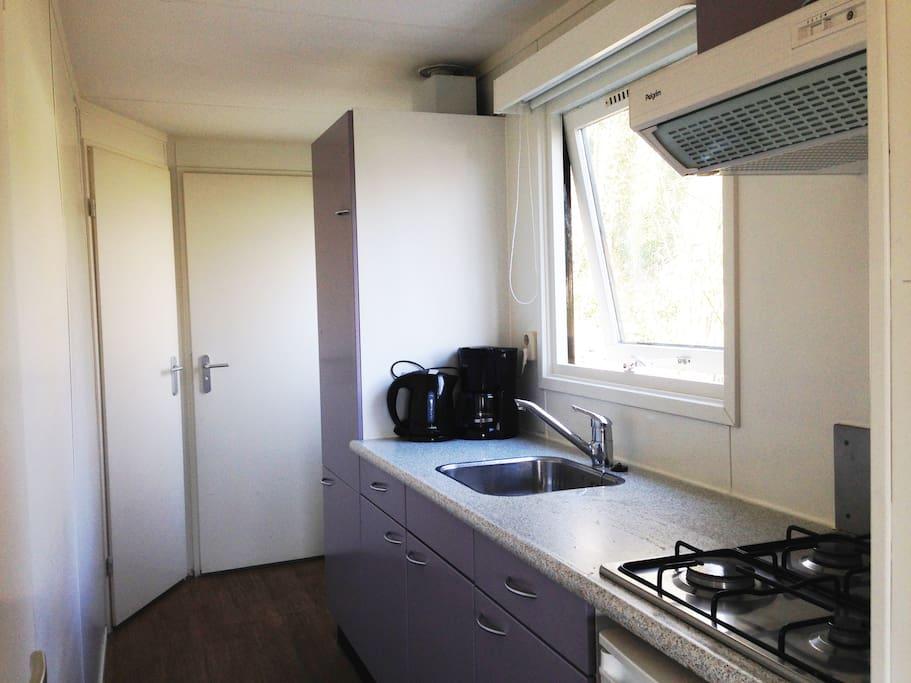 Keuken met fornuis, koelkast met kleine diepvries, waterkoker en koffiezetapparaat.