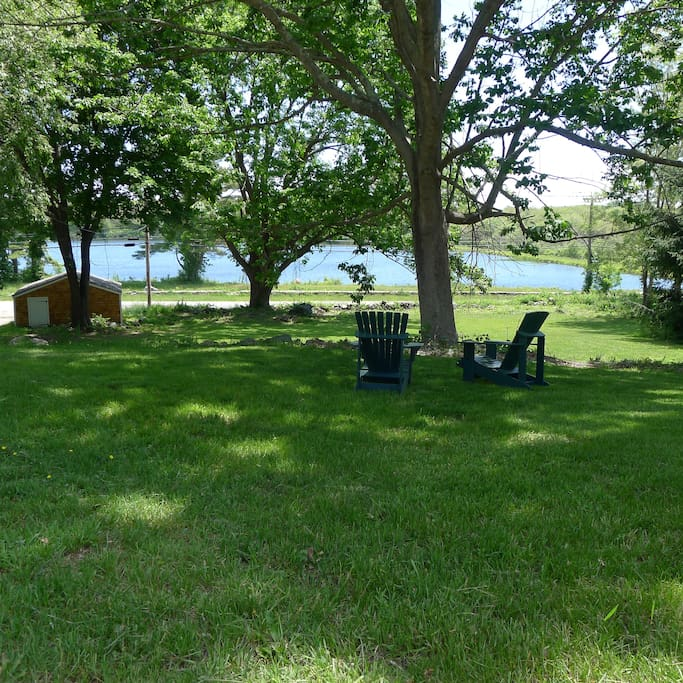 Adirondack chairs under large shade trees overlooking the reservoir.