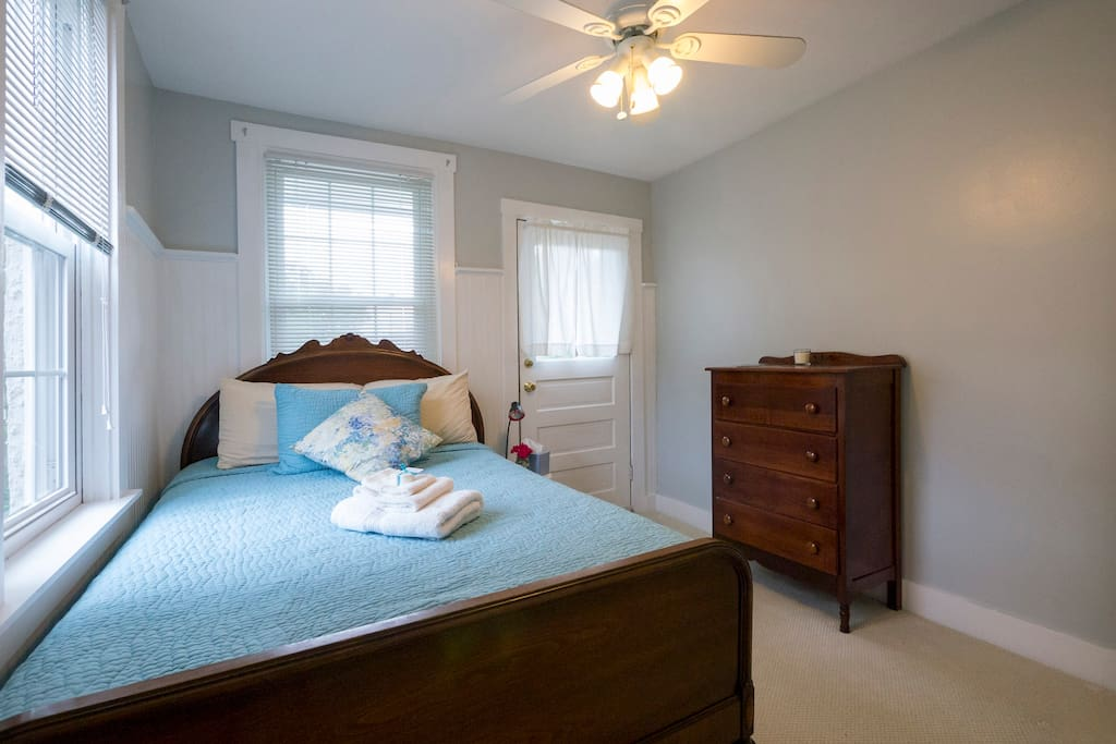 Your room with a full bed, a dresser, built-in closet, and a view of our quaint back yard.