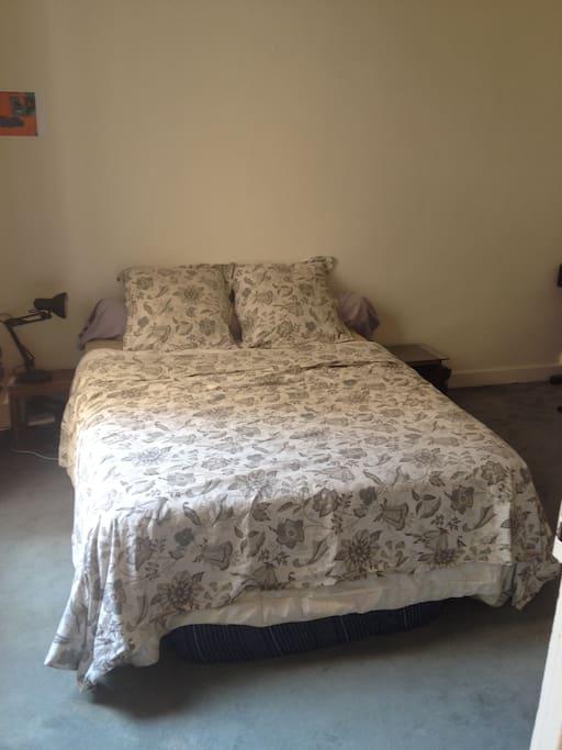 Un lit deux places avec un matelas d'appoint.