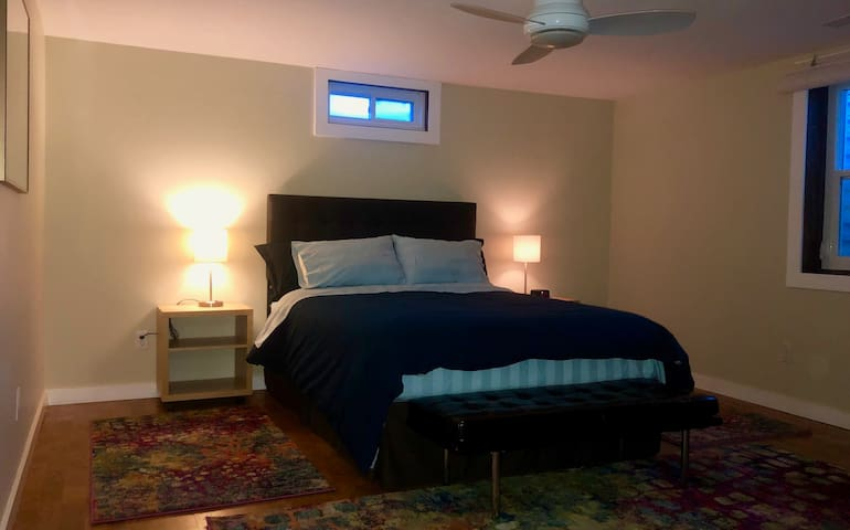 Large bedroom with queen bed and plush, cozy bedding.