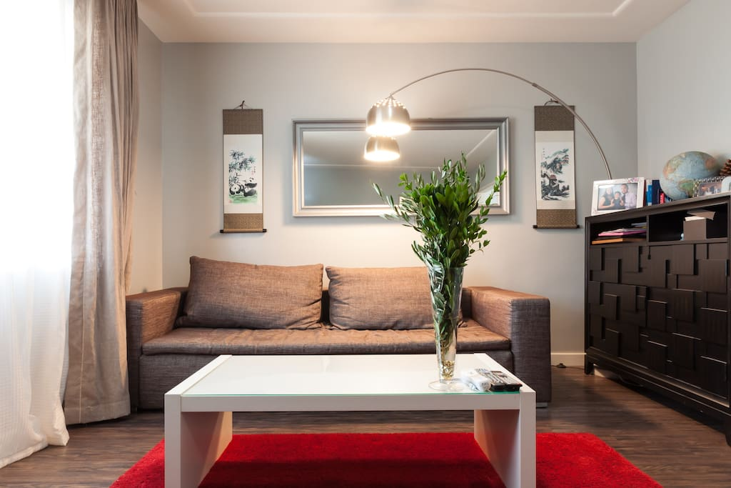 Living room, includes a 75 inch 4K cable TV, a comfortable modern Bo-Concept sofa, kids toys area.