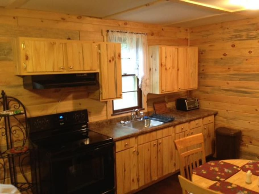 Nicely-equipped kitchen with stove, toaster oven and coffee maker (no microwave), stocked with dishes, pots, pans and silverware.  Fridge is on the back porch