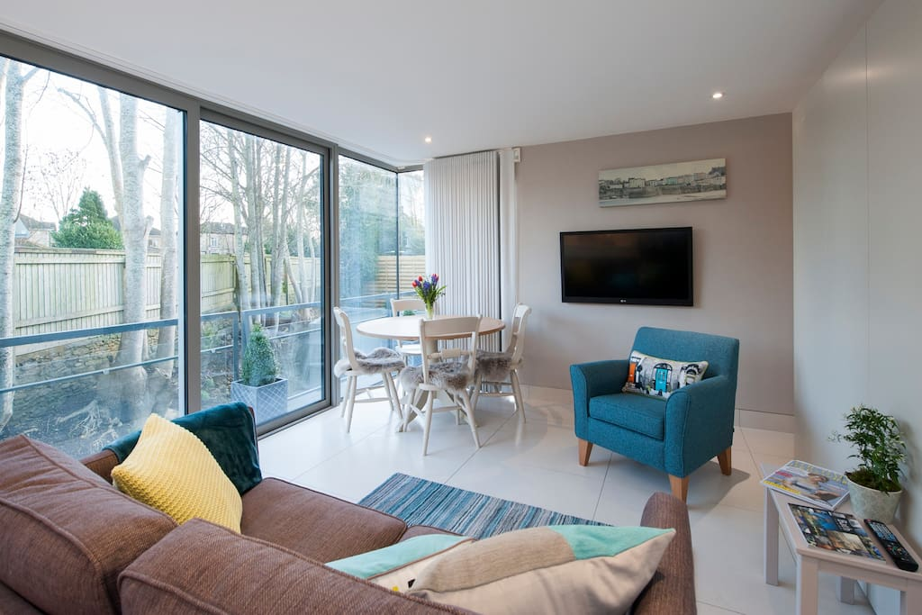 The living room is light and spacious with underfloor heating, comfortable seating and electric curtains.