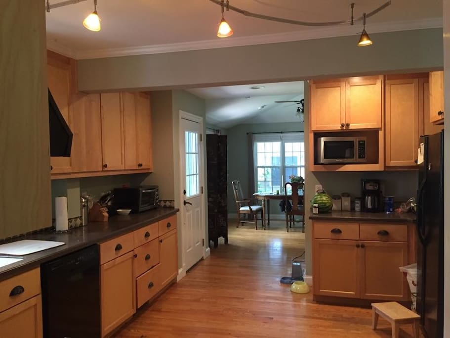 Spacious, modern kitchen with dining table and access to screened in back porch/back patio with additional dining for 8.