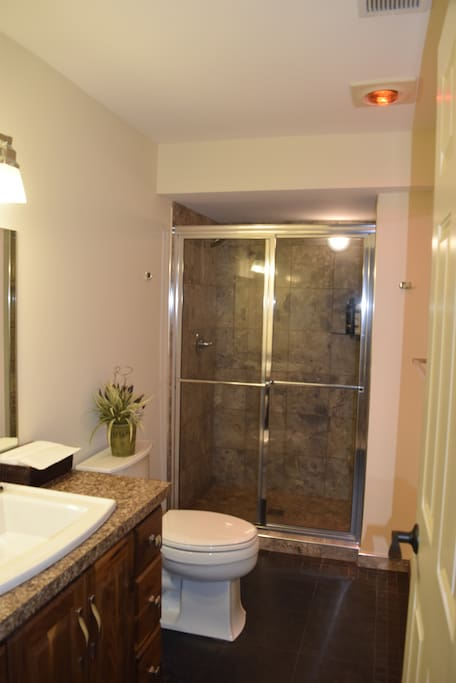 Bathroom with shower with heated tile flooring. The bathroom is located across from your room.