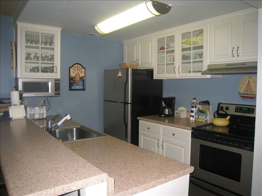 Kitchen with dishwasher, microwave and electric stove.