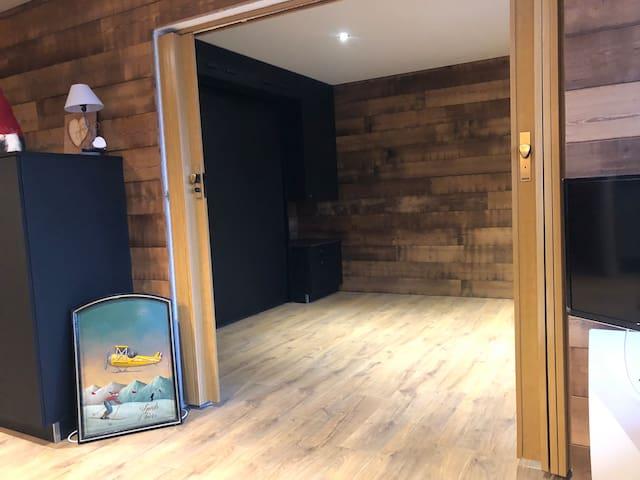 Vue du salon sur la chambre avec le lit fermé
