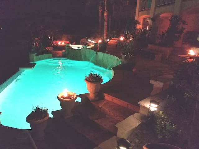 Pool and surroundings illuminated with TIKI fires lit at night.