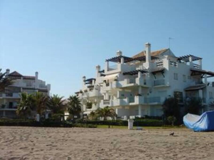 Small complex straight through gardens onto sandy beach