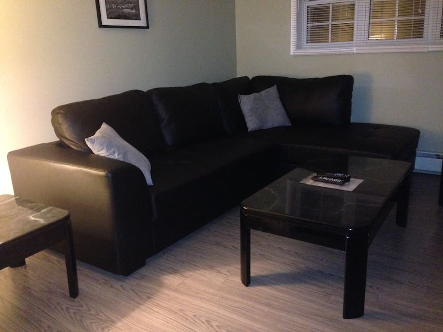 Black leather sectional in living-room.