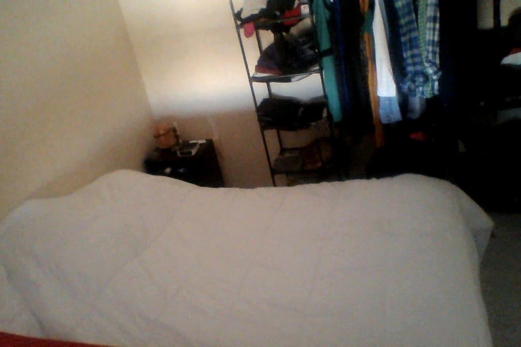 Chambre avec grand lit séparée par un rideau.