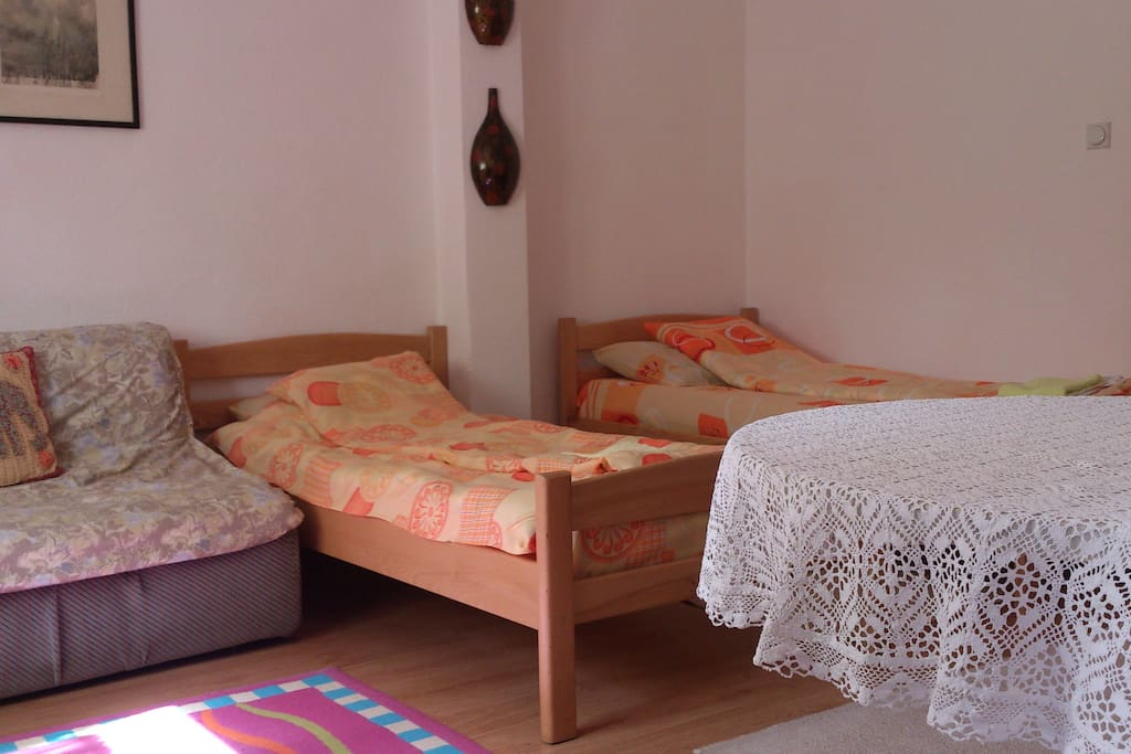 Spacious room with two beds and sofa, wardrobe and dinning table