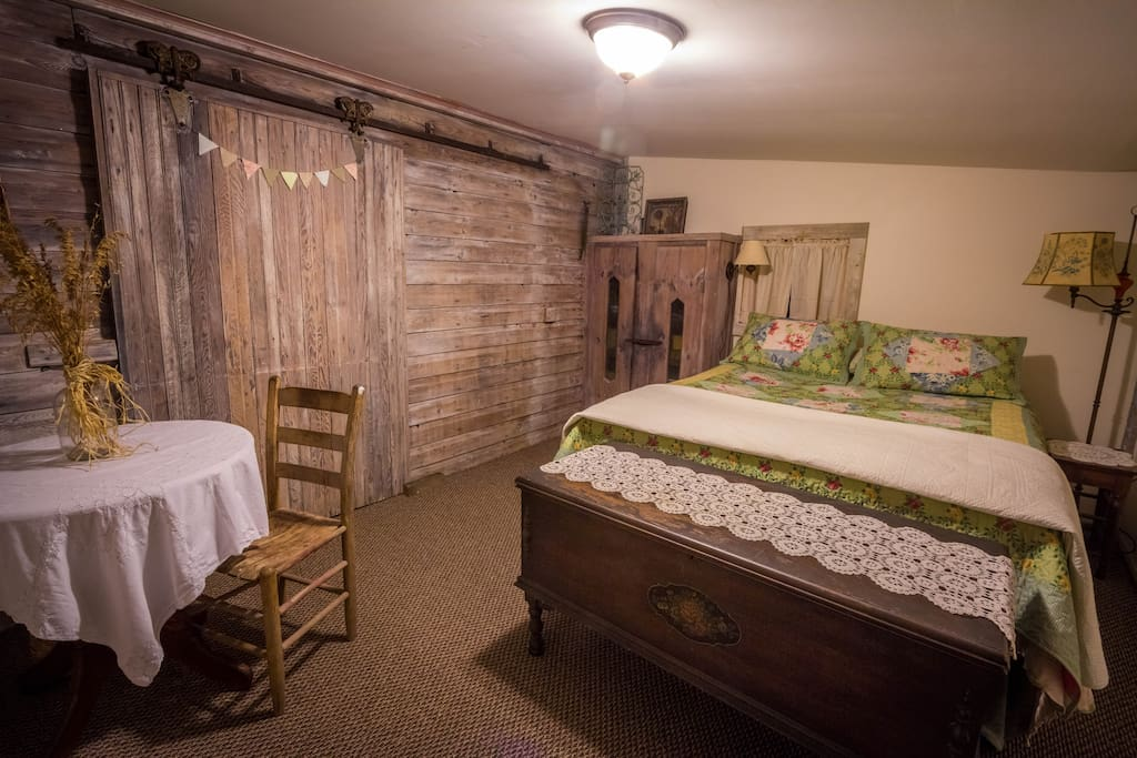 The Rose Room has a comfy queen bed, table, bookshelf, a/c. Check out the cool barn door!